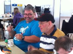 Zwei FROG-Mitglieder am Tisch sitzend mit einer Tasse Kaffe vor ihnen