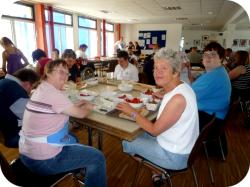 Am Tisch sitzende Personen beim Erdbeeren entstilen