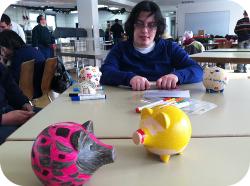 Ein Tisch; im Vordergrund zwei fertig bemalte Sparschweine, im Hintergrund ein FROG-Mitglied am Tisch sitzend