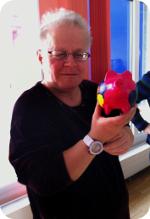 FROG-Mitglied, welches stolz sein fertig bemaltes Sparschwein in die Kamrea hält