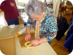 Eine ältere Frau, die gerade einen kunstvoll geflochtenen Teigring herstellt