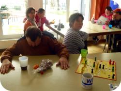"""Im Vordergrund sitzen zwei Personen an einem Tisch und spielen """"Mensch ärgere Dich nicht"""". Im Hintergrund sitzen vier Personen an einem Tisch und reden miteinander."""