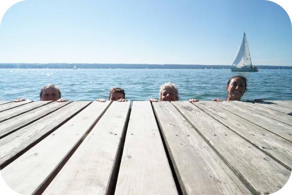 4 Personen, die sich im Wasser befinden und über den Rand des Stegs schauen