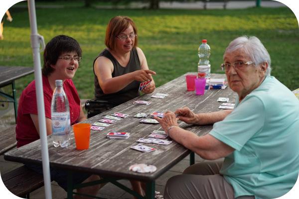 3 Frauen beim Kartenspielen, draussen an einem Holztich und Holzbänken