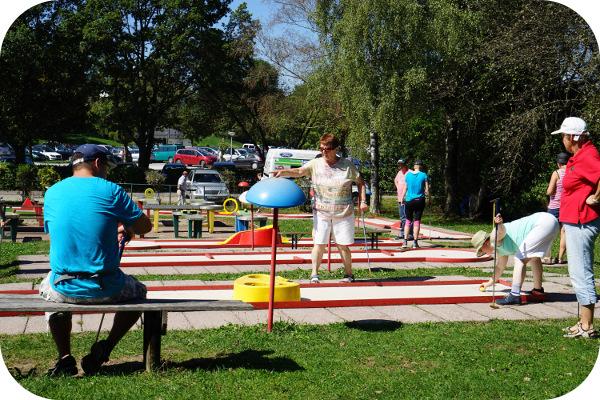 Mehrere Personen beim Minigolf spielen