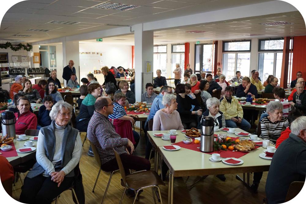 Veranstaltungsraum der WEK mit vielen Gästen die an mehreren Tischen sitzen und Kaffee und Hefezopf genießen
